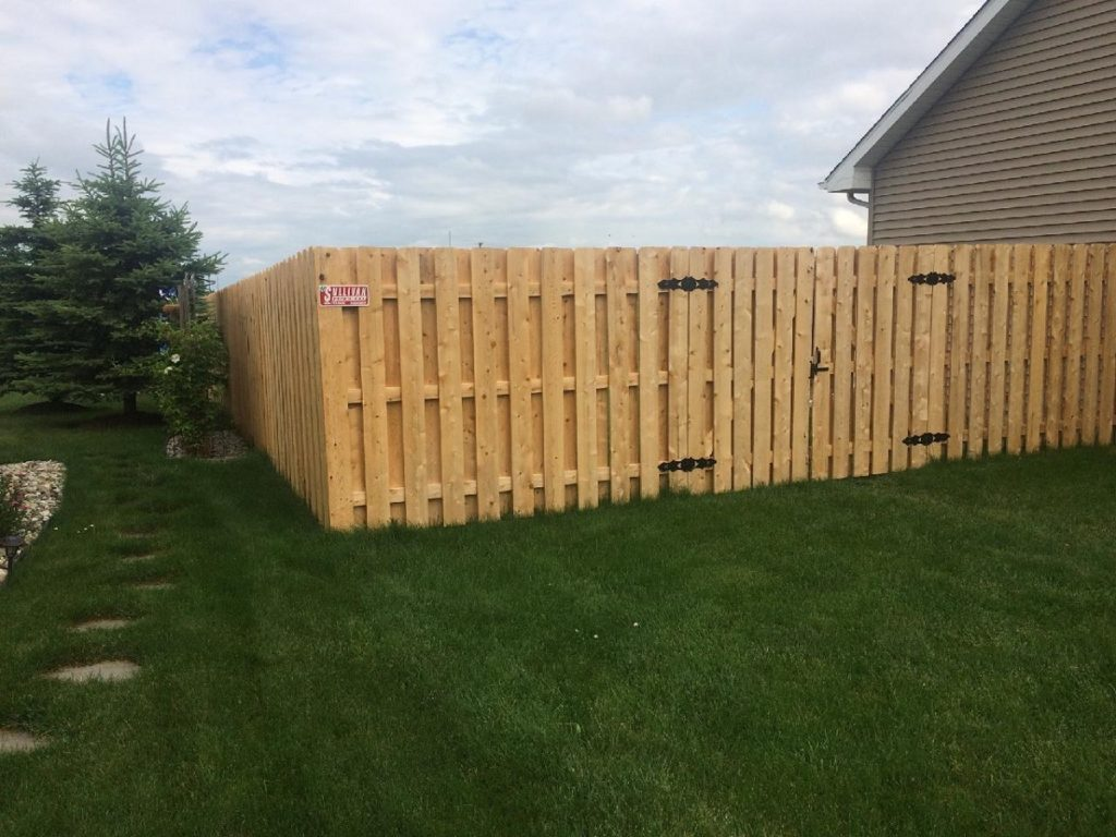 Tall wooden fence on fresh cut grass